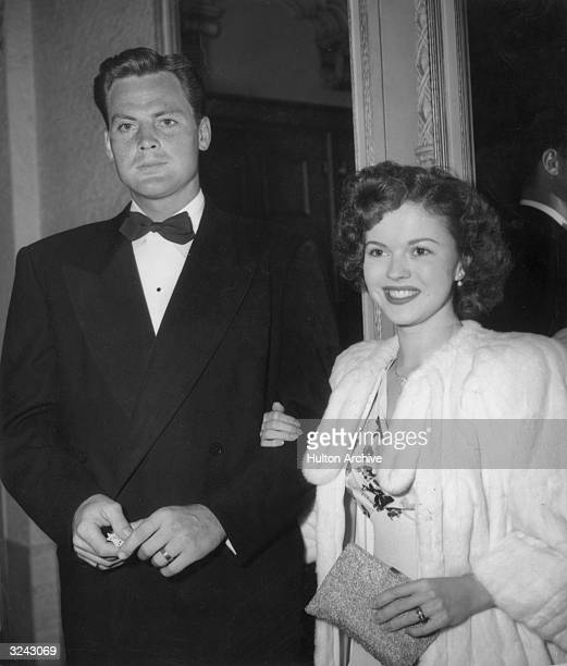 Actors and married couple Shirley Temple and John Agar standing smiling and wearing evening clothes as they attend the premiere of the movie by...
