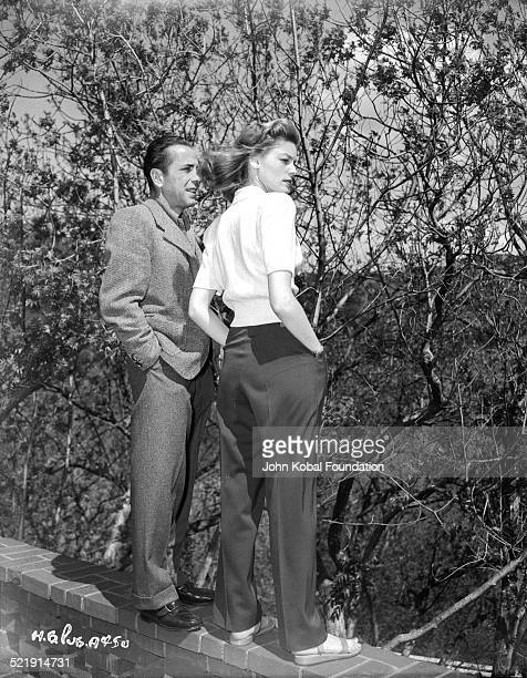 Actors and spouses Humphrey Bogart and Lauren Bacall standing together on a wall, for Warner Bros Studios, 1945.