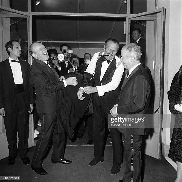 Actors Andre Bourvil Louis de Funes and Terry Thomas at a premiere during the Cannes Film Festival in May 1966 in CannesFrance