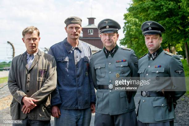 Actors Andreas Lust Ulrich Brandhoff as prisoner Heinrich Schuepp Robert Gallinowski and Rainer Bock stand in front of the former concentration camp...