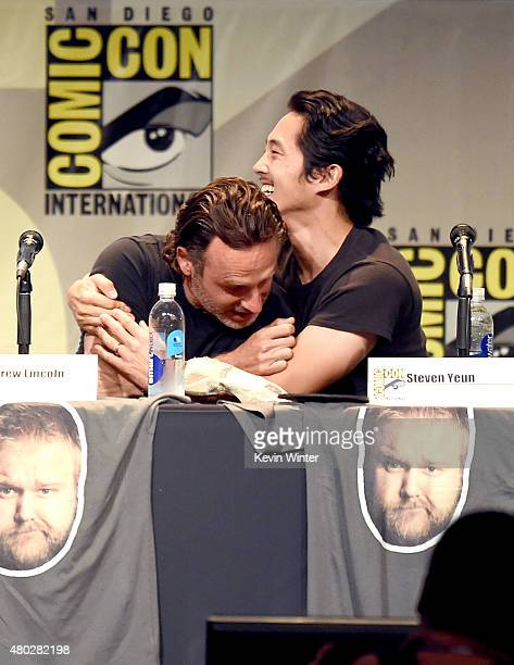 Actors Andrew Lincoln and Steven Yeun embrace onstage at AMC's 'The Walking Dead' panel during ComicCon International 2015 at the San Diego...