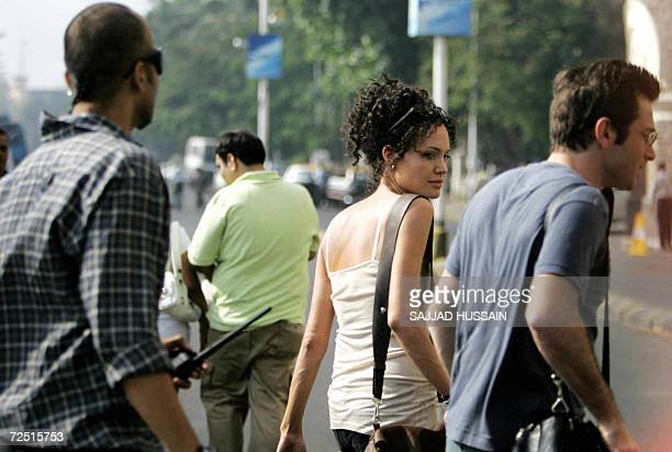 US actors Angelina Jolie and Dan Futterman are escorted by a bodyguard as they walk on location during a film shoot in Mumbai 13 November 2006 Jolie...