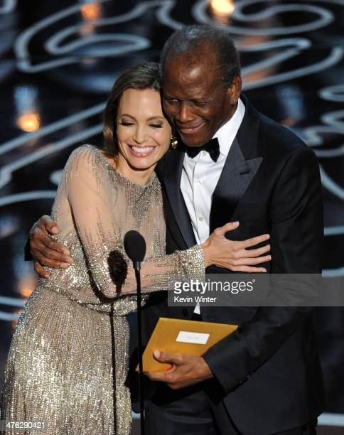 Actors Angelina Jolie and Sidney Poitier walk onstage during the Oscars at the Dolby Theatre on March 2 2014 in Hollywood California