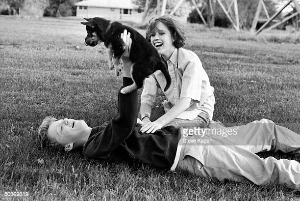 Actors Anthony Michael Hall and Molly Ringwald playing w puppy during break in location shooting of The Breakfast Club