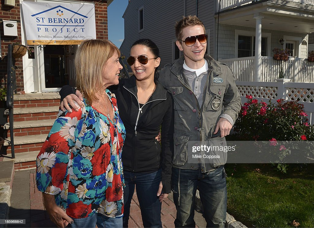 Actors Archie Panjabi (L) and Matt Czuchry pose for a picture with a victim of Hurricane Sandy as The Cast Of 'The Good Wife' Celebrates Their100th Episode With A Day Of Service For The St. Bernard Project on October 26, 2013 in New York City.