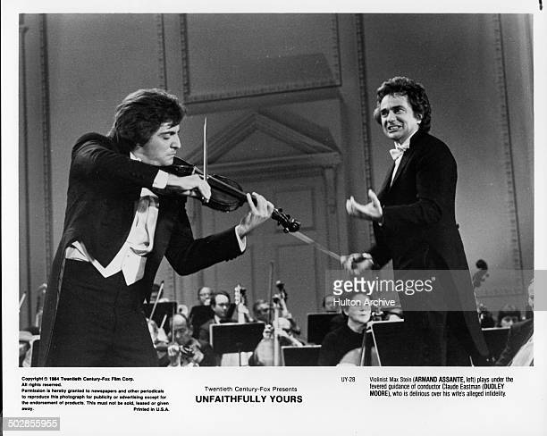 Actors Armand Assante plays the violin and Dudley Moore conducts in a scene during the 20th Century Fox movie ' Unfaithfully Yours' circa 1984