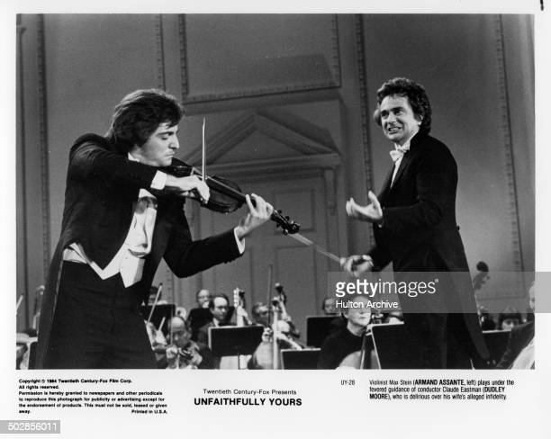 Actors Armand Assante plays the violin as Dudley Moore conducts him in a scene during the 20th Century Fox movie ' Unfaithfully Yours' circa 1984