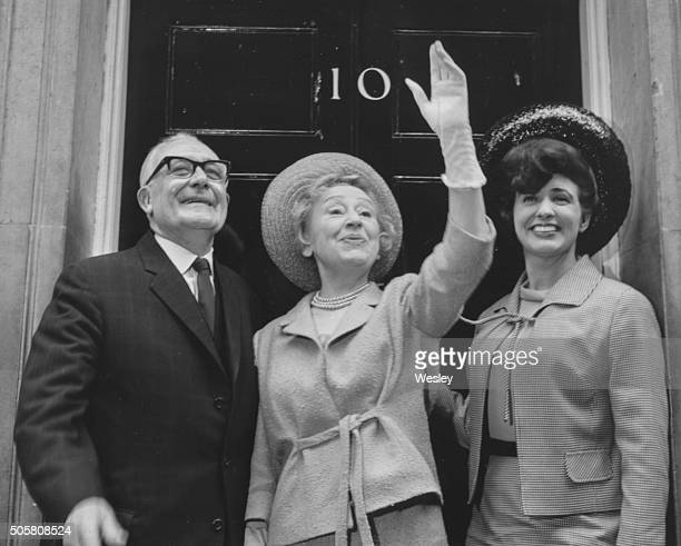 Actors Arthur Leslie and Doris Speed and Pat Phoenix, stars of the ITV soap opera 'Coronation Street', pictured waving from outside 10 Downing Street...