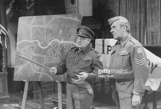 Actors Arthur Lowe and John Le Mesurier inspecting a map in a scene from episode 'Battle of the Giants' of the television sitcom 'Dad's Army'...
