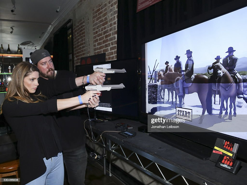 Actors Ashley Greene (L) and Tanner Beard play 6 Bullets to Hell at the '6 Bullets To Hell' Mobile Game Launch Party on May 10, 2016 in Los Angeles, California.