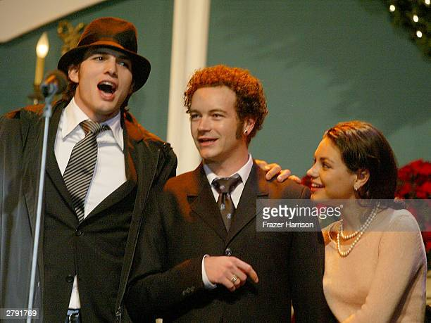 Actors Ashton Kutcher Danny Masterson and Mila Kunis perform on stage at the Church of Scientology's 11th Annual Christmas Stories Fundraiser to...