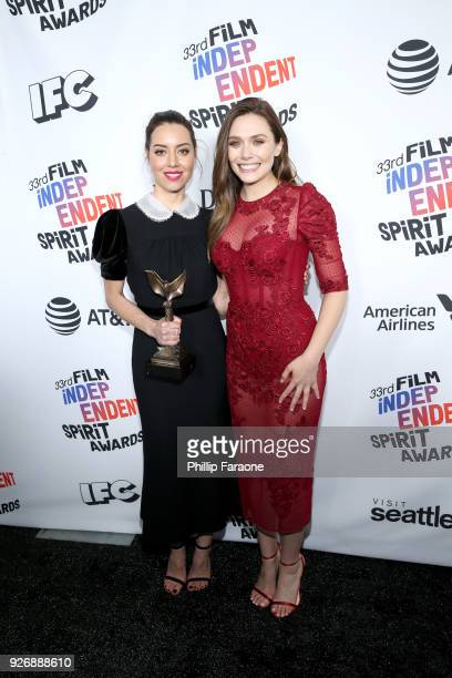Actors Aubrey Plaza and Elizabeth Olsen pose with the Best First Feature award for 'Ingrid Goes West' in the press room during the 2018 Film...