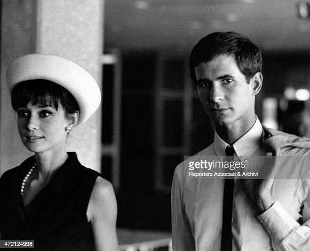 'Actors Audrey Hepburn and Anthony Perkins are photographed together side by side she wears a fashionable white hat and a pearl necklace while he...