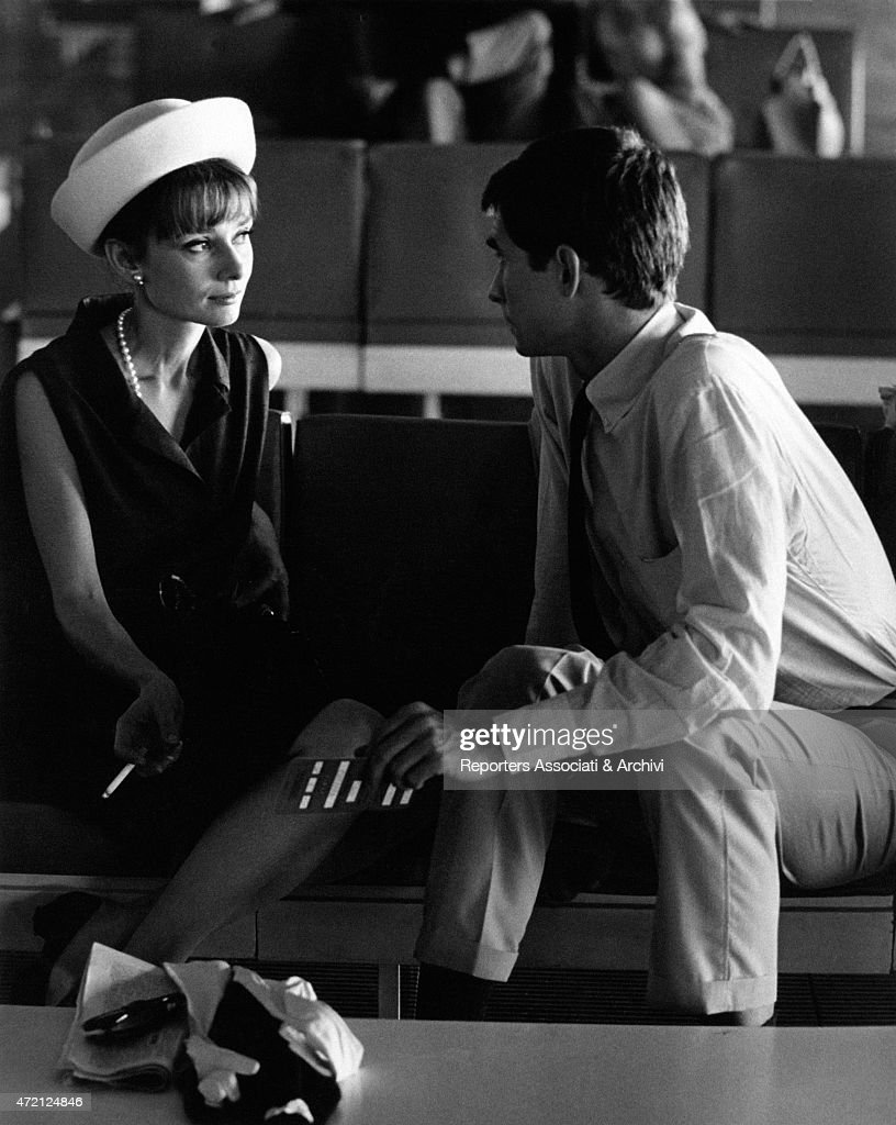 'Actors Audrey Hepburn and Anthony Perkins are sitting waiting at the airport and talk; she smokes a cigarette and wears a fashionable white hat and a pearl necklace. Paris (France), July 1962. (Photo by Pierluigi Praturlon\Reporters Associati & Archivi\Mondadori Portfolio via Getty Images)'
