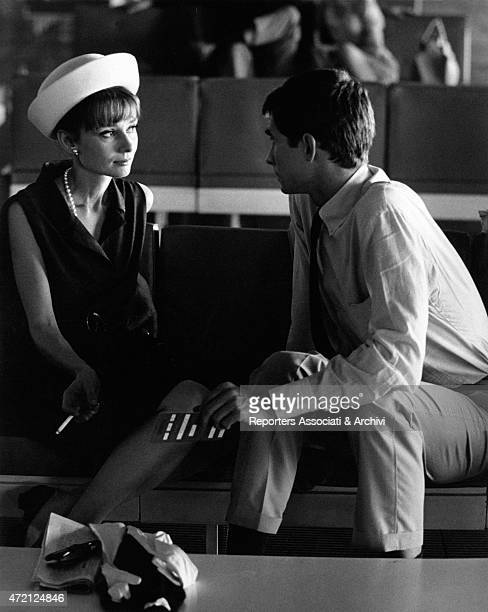 'Actors Audrey Hepburn and Anthony Perkins are sitting waiting at the airport and talk she smokes a cigarette and wears a fashionable white hat and a...