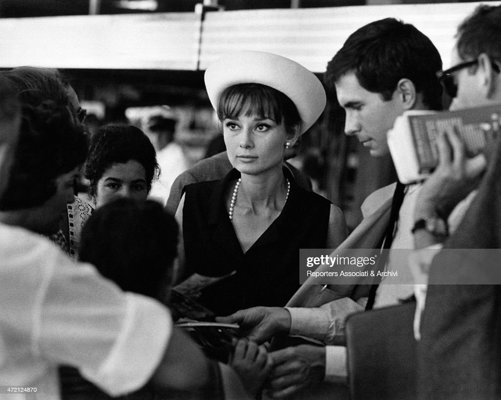 'Actors Audrey Hepburn and Anthony Perkins, just landed at the airport, are surrounded by their admirers; the movie stars of Roman Holiday and Psycho are busy signing autographs. Paris (France), July 1962. (Photo by Pierluigi Praturlon\Reporters Associati & Archivi\Mondadori Portfolio via Getty Images)'