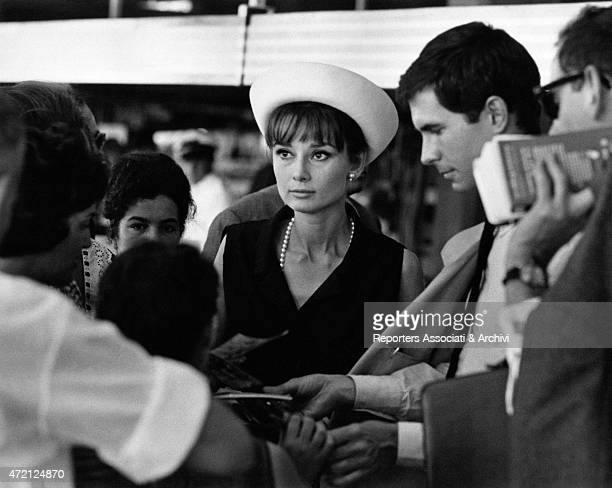 'Actors Audrey Hepburn and Anthony Perkins just landed at the airport are surrounded by their admirers the movie stars of Roman Holiday and Psycho...