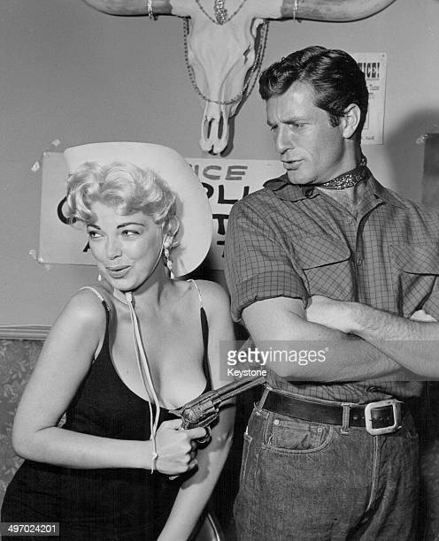Actors Barbara Nichols and Hugh O'Brian dressed as cowboys with toy guns as part of a charity fund raiser Hollywood circa 19551965