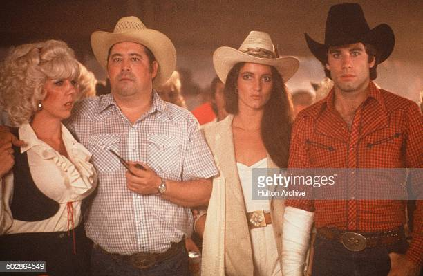 Actors Barry Corbin with actress Madolyn Smith Osborne and John Travolta stand in a scene during the Paramount Pictures movie 'Urban Cowboy circa 1980