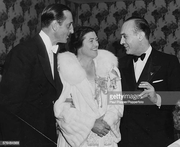 Actors Basil Rathbone , Lotte Lehmann and Charles Boyer pictured chatting together at a black-tie event in the United States circa 1940.