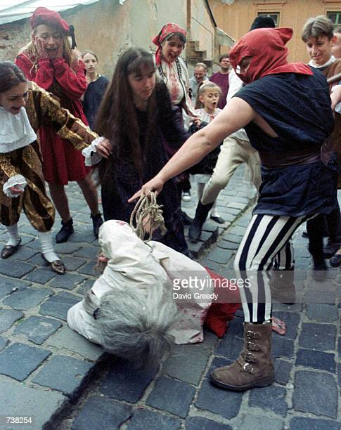 """Actors beat a """"witch"""" after she fell en route to her mock trial May 9, 2001 in the center of the Translyvanian city of Sighisoara, Romania. The city..."""
