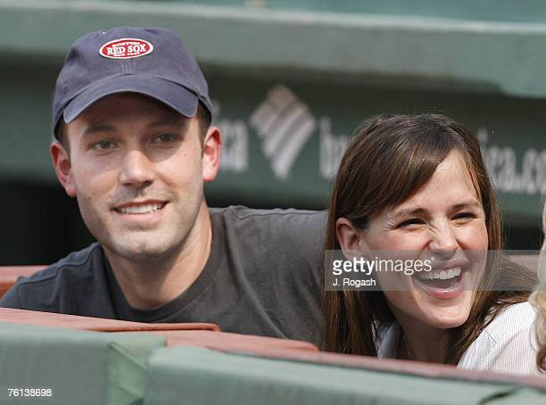 Actors Ben Affleck and Jennifer Garner smile while next to the Boston Red Sox dugout prior to the start of their baseball game against the New York...