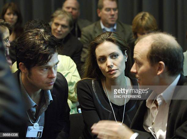 Actors Brad Pitt and Angelina Jolie listen to an unidentified man while sitting with the audience at the session 'Next steps for Africa' at the World...
