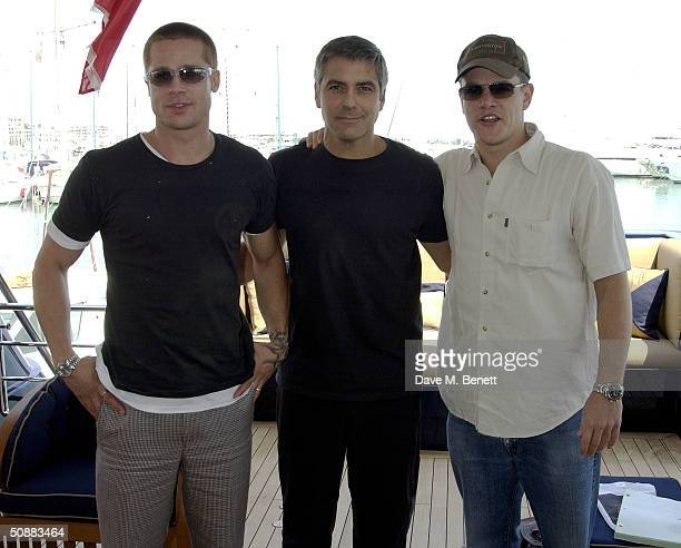 actors Brad Pitt George Clooney and Matt Damon stand aboard the Jaguar racing yacht to promote their new film 'Oceans 12' on May 21 2004 in Monte...
