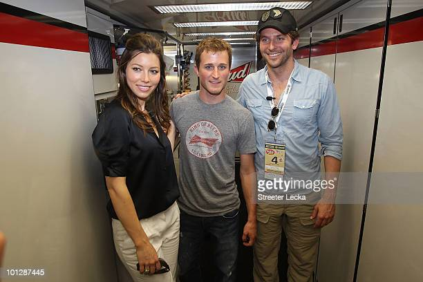 Actors Bradley Cooper and Jessica Biel pose with Kasey Kahne driver of the Budweiser/Armed Forces Tribute Ford in the team hauler prior to the NASCAR...