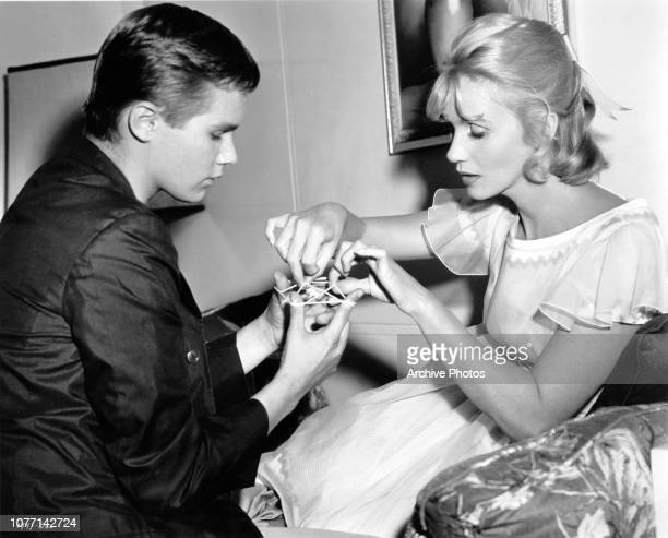 Actors Brandon De Wilde and Eva Marie Saint play a game of cat's cradle on the set of the MGM film 'All Fall Down', 1961.
