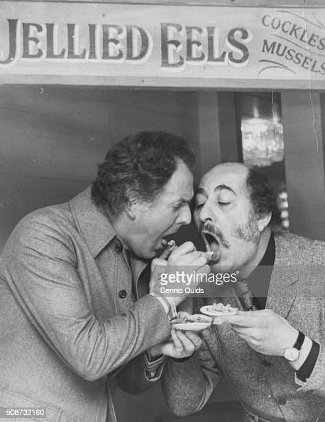 Actors Brian Rix and Alfred Marks feeding each other jellied eels at a seafood stall as they celebrate their birthdays together during a break from...