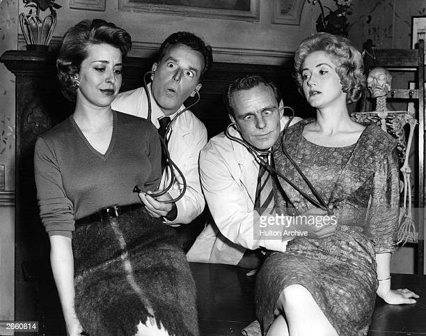 Actors Brian Rix and Dickie Henderson checking the heart rates of Helen Jessop and Liz Fraser respectively during a scene from the play 'Doctor in...