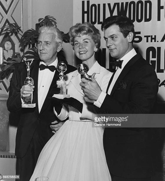 Actors Buddy Adler Doris Day and Tony Curtis with their statuettes at the Foreign Press Awards or the Golden Globes in Hollywood 1958