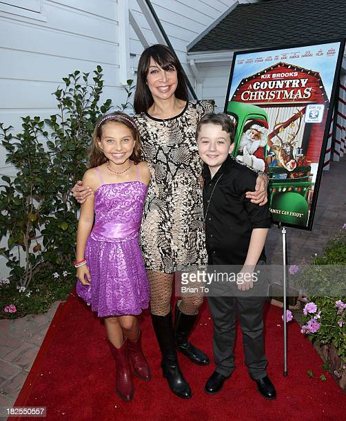 Actors Caitlin Carmichael Illeana Douglas and Benjamin Stockham attend A Country Christmas Los Angeles Special Screening at The DeMille Theatre on...