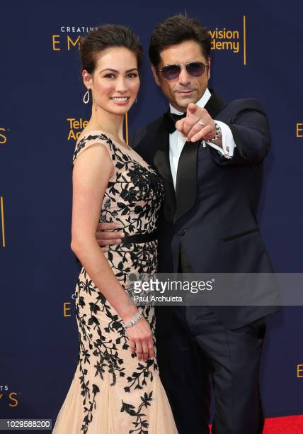 Actors Caitlin McHugh and John Stamos attend the 2018 Creative Arts Emmy Awards at Microsoft Theater on September 8 2018 in Los Angeles California