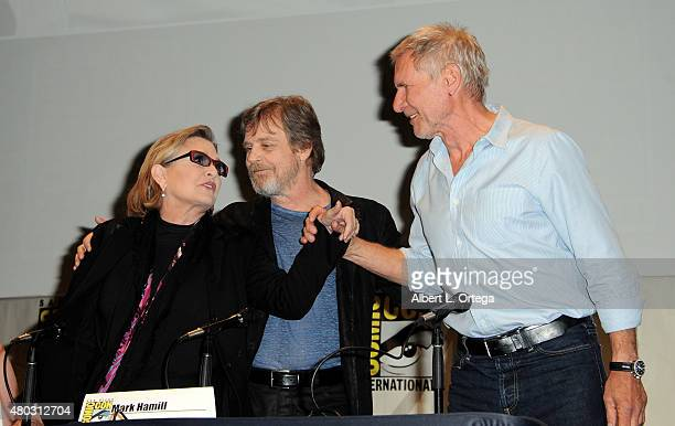 Actors Carrie Fisher Mark Hamill and Harrison Ford greet onstage at the Lucasfilm panel during ComicCon International 2015 at the San Diego...