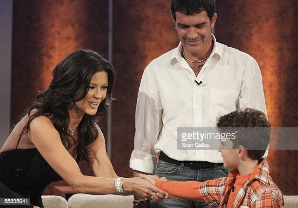 Actors Catherine ZetaJones and Antonio Banderas greet child contestant Florian Osmani during the live broadcast of 'Wetten dass' on ZDF television at...