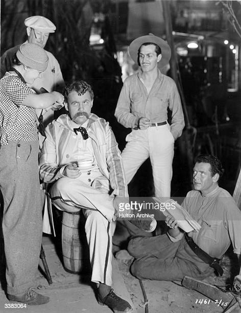 Actors Charles Laughton Kent Taylor and Charles Bickford prepare to shoot the film 'White Woman' directed by Stuart Walker for Paramount