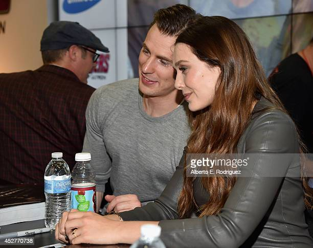 Actors Chris Evans and Elizabeth Olsen attends Marvel's Avengers Age Of Ultron Hall H Panel Booth Signing during ComicCon International 2014 at San...