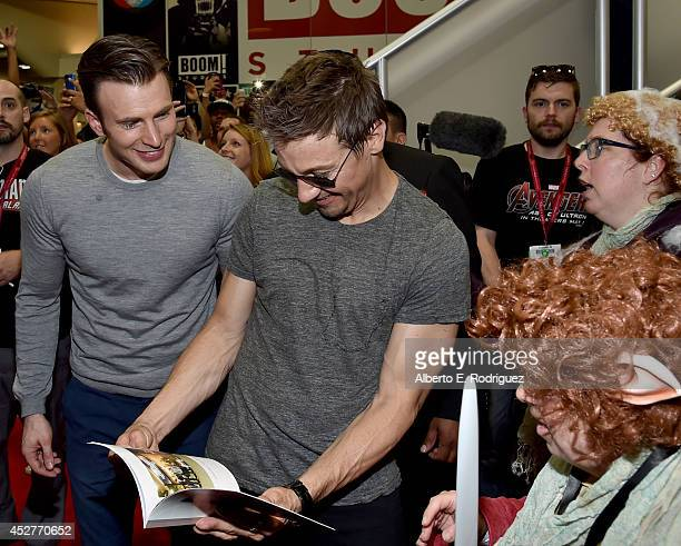 Actors Chris Evans and Jeremy Renner attend Marvel's Avengers Age Of Ultron Hall H Panel Booth Signing during ComicCon International 2014 at San...