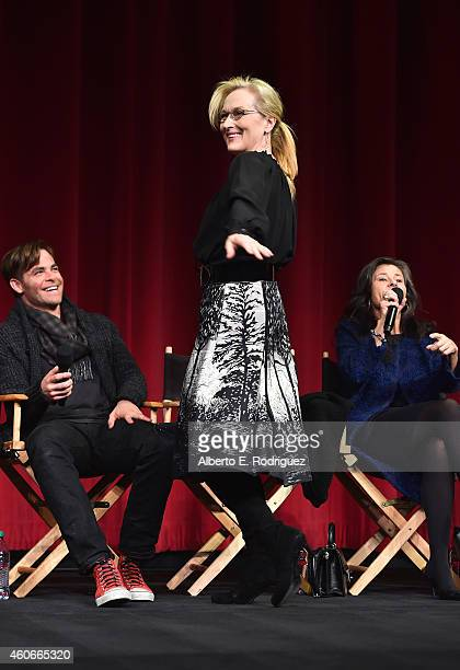 Actors Chris Pine and Tracey Ullman look on as Meryl Streep shows her dress to the audience onstage during the Into the Woods All Guild Q A at AMPAS...