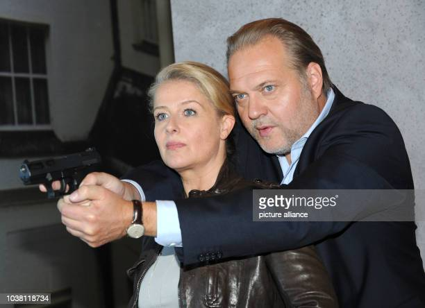 Actors Christina Rainer and Jan-Gregor Kremp pose for the camera with a gun during the shooting of the crime series 'Der Alte' by German broadcaster...
