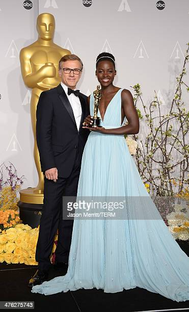 Actors Christoph Waltz and Lupita Nyong'o winner of Best Performance by an Actress in a Supporting Role poses in the press room during the Oscars at...
