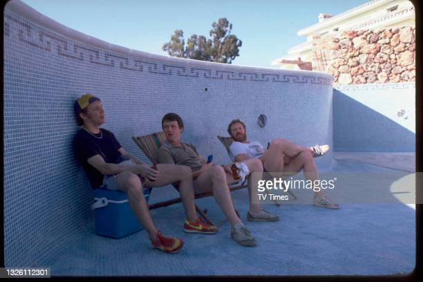 Actors Christopher Fairbank, Kevin Whately and Pat Roach sitting in an empty swimming pool on the set of comedy drama series Auf Wiedersehen, Pet,...