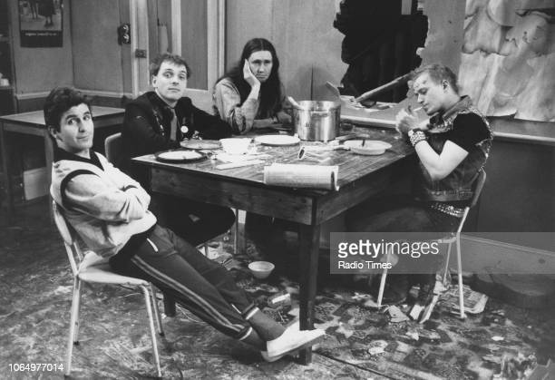 Actors Christopher Ryan, Rik Mayall, Nigel Planner and Adrian Edmondson sitting around a table in a scene from the television sitcom 'The Young...