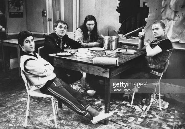Actors Christopher Ryan Rik Mayall Nigel Planner and Adrian Edmondson sitting around a table in a scene from the television sitcom 'The Young Ones'...