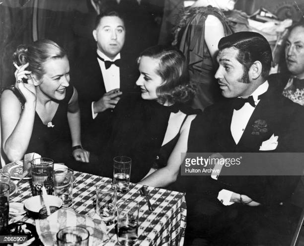 Actors Clark Gable and Carole Lombard who were married the same year dine out with Eddie Adams