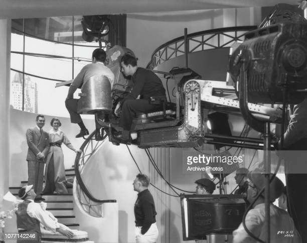 Actors Clark Gable and Myrna Loy on the set of the MGM film 'Wife Vs. Secretary', 14th December 1935. Director Clarence Brown stands under the camera...