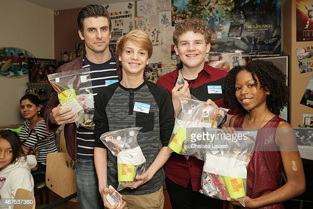 Actors Cooper Barnes Jace Norman Sean Ryan Fox and Riele Downs prepare swag bags for the children as they bring the Kids Choice Awards experience to...