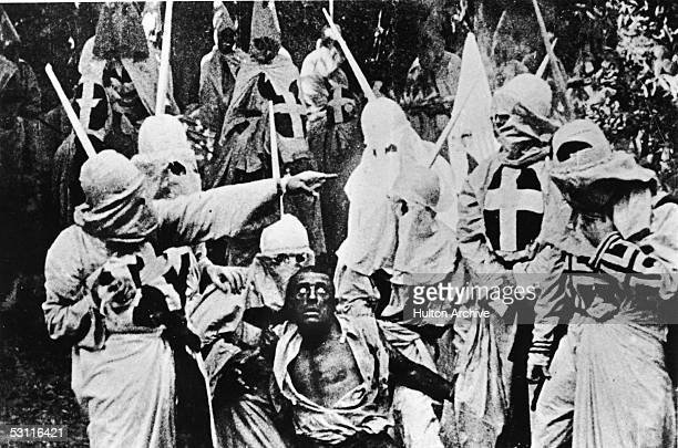 Actors costumed in the full regalia of the Ku Klux Klan chase down a white actor in blackface in a still from 'The Birth of a Nation' the firstever...